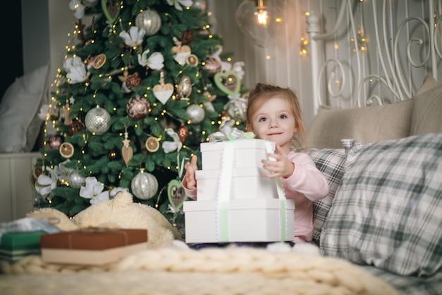 Niña hermosa con sus regalos se sienta en su cama. ella abraza sus manos cajas de regalo de navidad