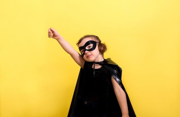 Niña héroe en una máscara y capa en una pared amarilla