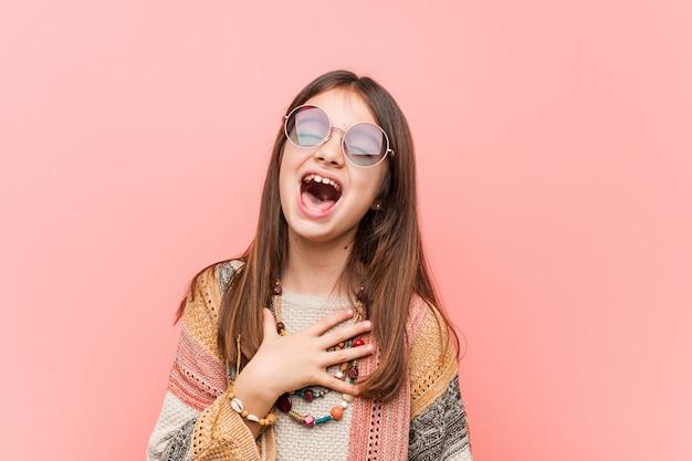 La niña hippie se ríe a carcajadas manteniendo la mano en el pecho.