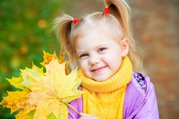 Niña con hoja amarilla de otoño en manos