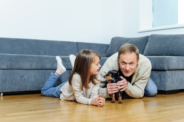 La niña y el hombre con el cachorro están en el suelo de la habitación.