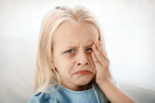 Niña indefensa llorando en el interior. concepto de abuso infantil