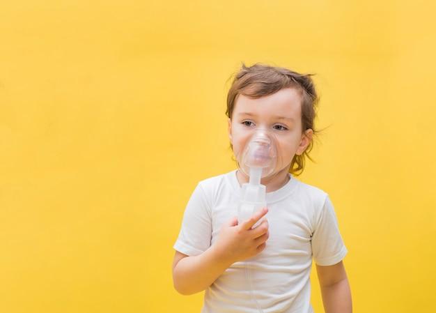 Una niña con un inhalador en un espacio amarillo con espacio de copia. linda chica rubia con una máscara en la cara. mirando a un lado.