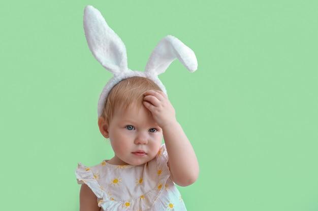 Una niña inquieta con orejas de conejo se rasca la frente con los ojos.