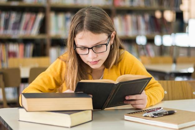 Niña inteligente leyendo en la biblioteca