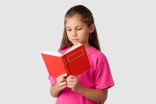 Niña inteligente leyendo libro rojo