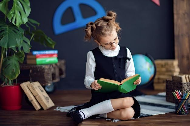 Niña inteligente leyendo libros de texto en la escuela