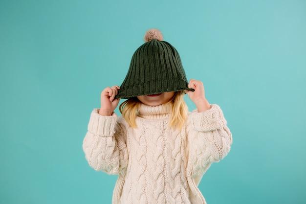 Niña en invierno sombrero y suéter en azul