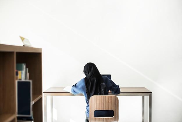 Niña islámica estudiando con una laptop