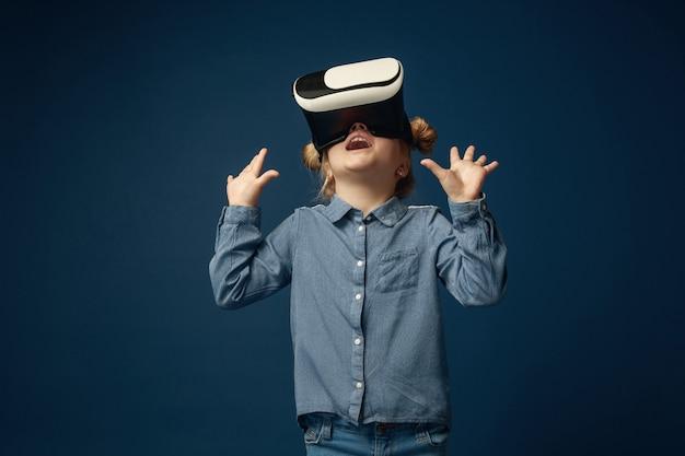 Niña en jeans y camisa con gafas de casco de realidad virtual