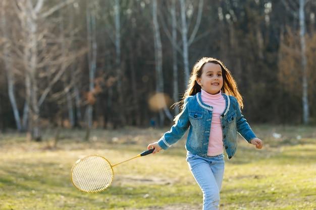 Niña en jeans jugando tenis en el parque