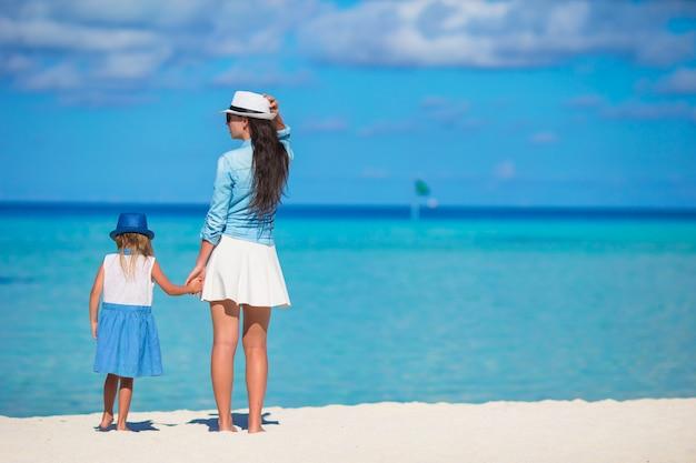 Niña y joven madre durante vacaciones en la playa