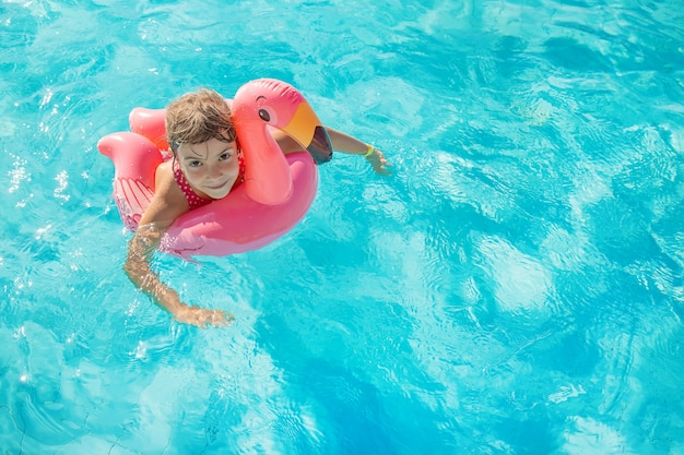 Niña joven, relajante, en la piscina
