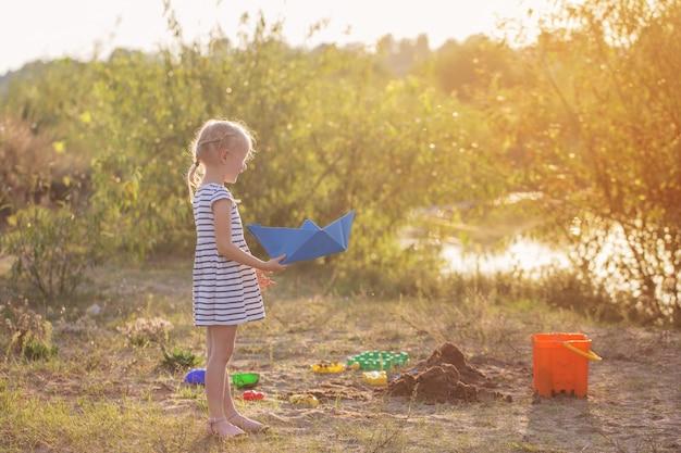 Niña juega en la arena con juguetes