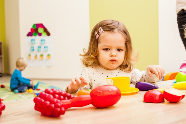 Niña juega con artículos para el hogar de los niños y frutas artificiales en la mesa. equipo de cocina