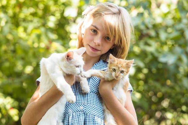 Niña juega con gatito al aire libre en el parque