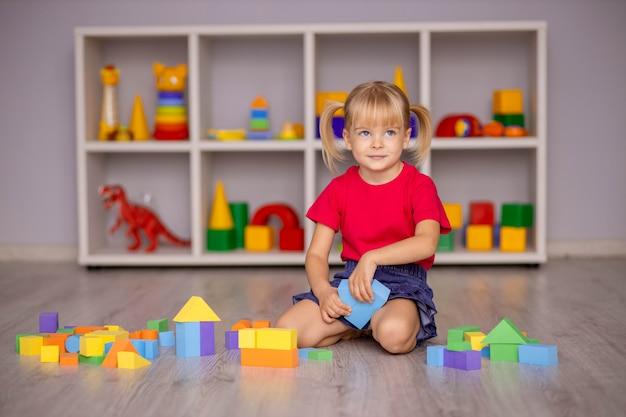 La niña juega con juguetes en casa, en la guardería o guardería. desarrollo infantil.