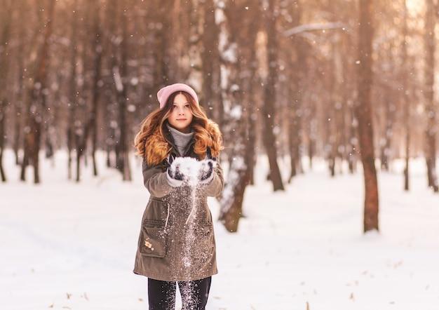 Niña juega con nieve en el parque en invierno