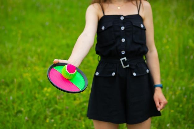 Una niña juega una pelota de tenis con velcro al aire libre. día libre, día soleado de verano. de cerca.