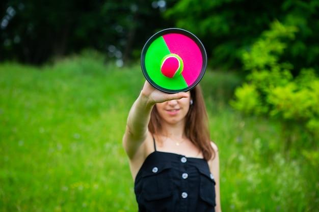 Una niña juega una pelota de tenis con velcro al aire libre. día libre, día soleado de verano.