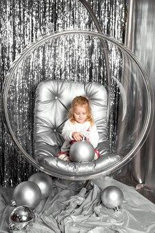 Niña juega en una silla un tazón de vidrio con bolas de plata