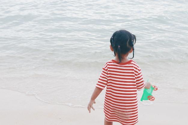 Niña jugando arena en la playa. filtro retro