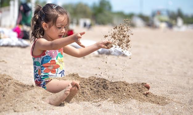 Niña jugando con arena en la playa. un niño alegre. el concepto de vacaciones de verano.