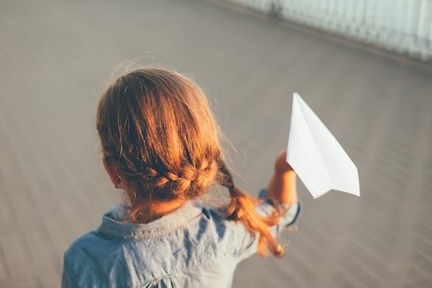 Niña jugando con avión de papel de juguete