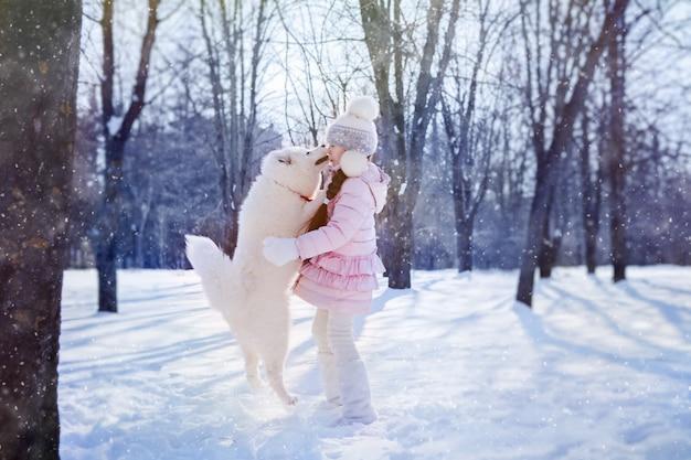 Niña jugando con un cachorro samoyedo en un parque cubierto de nieve en la mañana de navidad
