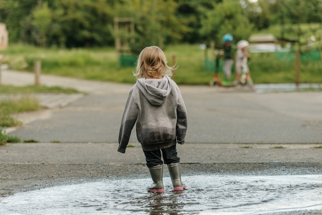 La niña está jugando en el charco con botas de goma.