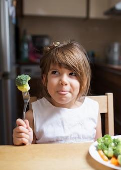 Niña jugando con comida saludable