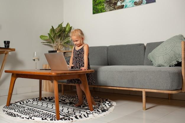Niña jugando en la computadora portátil. foto de alta calidad