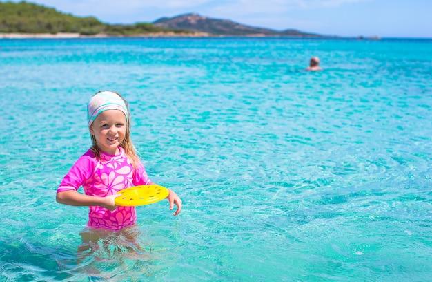 Niña jugando frisbee durante vacaciones tropicales en el mar