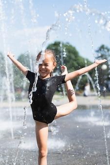 Niña jugando en la fuente de agua