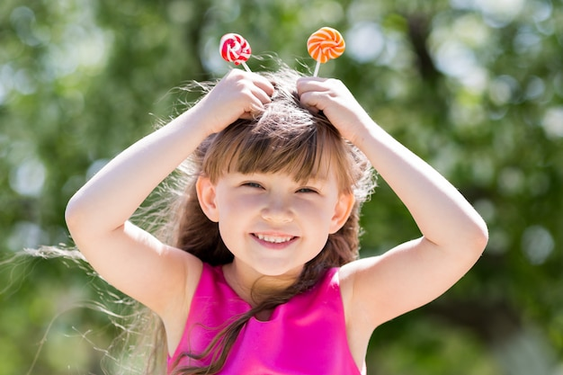 La niña está jugando con grandes dulces en un palo.