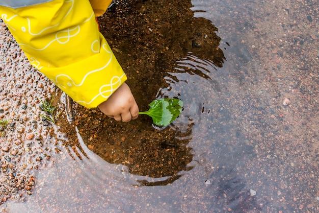Niña jugando con las hojas en un charco niña feliz niña jugando con hojas de otoño en un charco después de una lluvia.