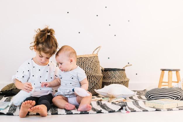 Niña jugando con lindo bebé