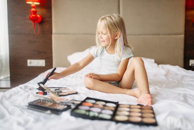 Niña jugando con maquillaje de mamás en dormitorio en casa. una infancia verdaderamente despreocupada, momentos felices