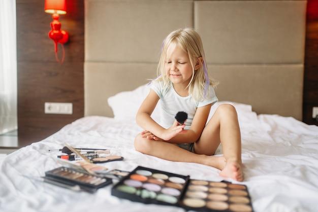 Niña jugando con maquillaje de mamás en dormitorio