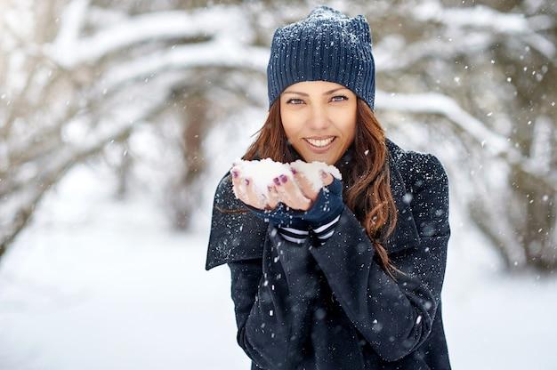 Niña jugando con nieve en el parque
