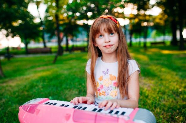 Niña jugando en un piano de juguete en el parque