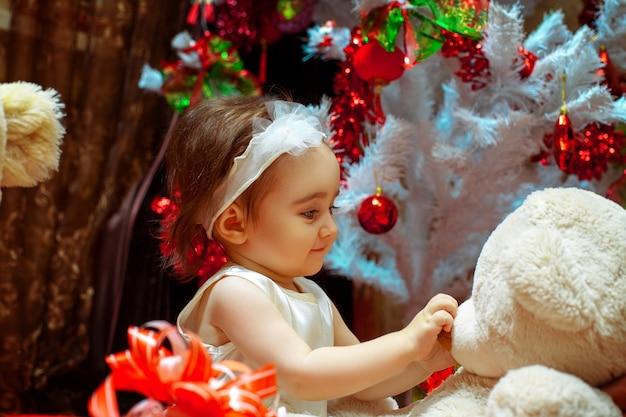 Niña jugando con su osito de peluche bajo el árbol de navidad blanco