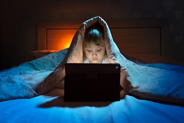 Niña jugando tablet debajo de la manta en la noche