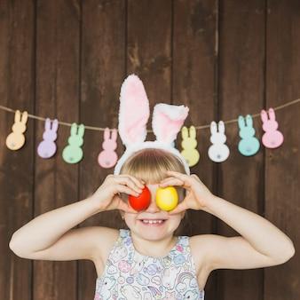 Niña juguetona en orejas de conejo con huevos