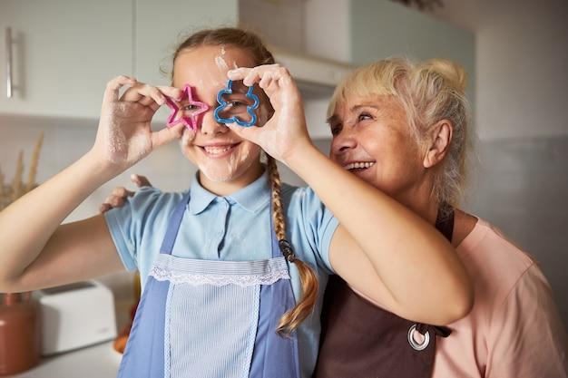 Niña juguetona y su abuela divirtiéndose con cortadores de galletas