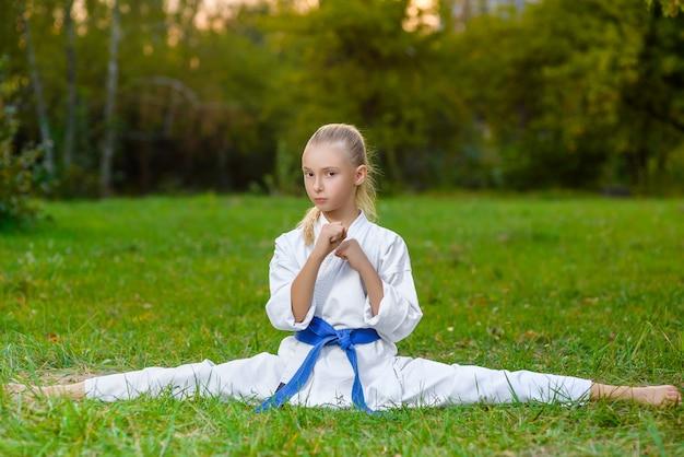Niña en kimono blanco durante el entrenamiento de ejercicios de karate en verano al aire libre
