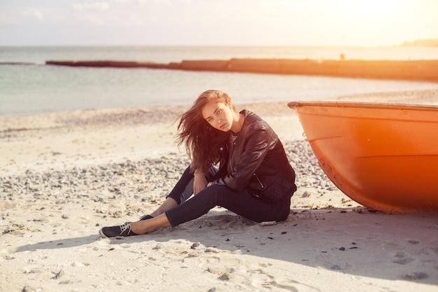 Una niña de lado cerca de un barco rojo en la playa junto al mar