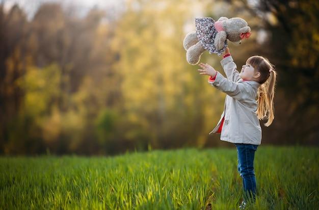 Niña lanza un osito de peluche en el parque y se ríe. copia espacio