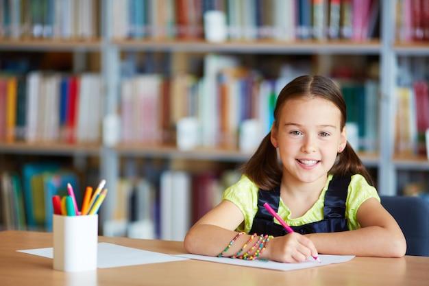 Niña con lápiz rosa en la biblioteca