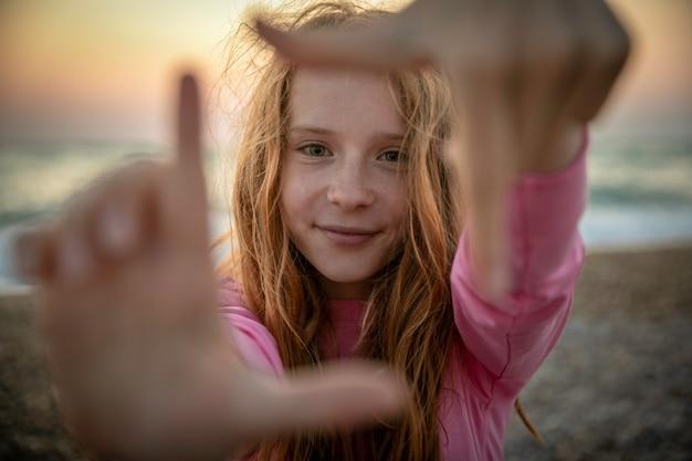 Una niña con largo cabello rojo y ojos verdes al atardecer junto al mar hace un marco de fotos con sus manos